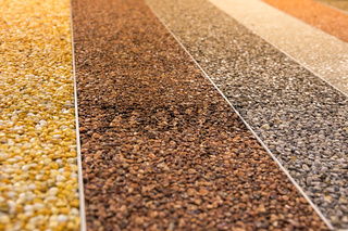 Close up of a natural stone carpet. Decorative stone coating. Slip resistant floor finish containing natural stone particles. Set of various types and colors.