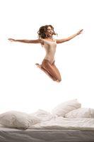 Happy slim model in bodysuit jumping over bed