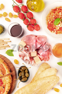 Italian food. Pizza, pasta, cheese, ham, capers, wine, tomatoes, overhead shot on a white background