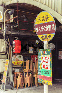 Restaurant sign immitating an old retro bus stop sign on underpass Yurakucho Concourse wall under the railway line of the station Yurakucho. Japanese noodle stalls and sake bars revive the nostalgic years of Showa air with old posters and placards glued t