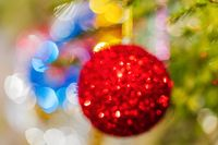 Defocused shining red Christmas ball hanging on branch of Xmas pine tree. Colorful blurred bokeh