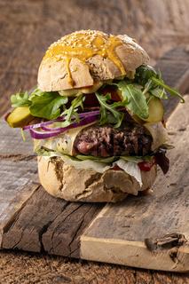 hausgemachter Cheeseburger auf dunklem Holz