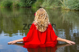 Blonde woman walks in natural water