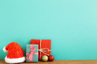 Christmas concept. Gift boxes with baubles, santa claus hat on wooden table with green background