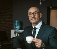 Mature business man in a business suit, holding a cup of coffee in a office building cafeteria having and looking at camera wearing expensive suit and eye glasses. Business concept