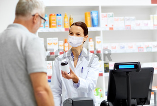 apothecary in mask and senior customer at pharmacy