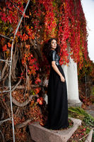 woman near the wall of autumn leaves