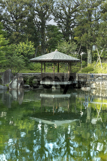 Grandmother came back for the obon festival that honors the spirits of the ancestors. She admires the pond by remembering the past near the exagonal Gazebo Ukimido in the central pond of Mejiro Garden where ducks are resting and which is surrounded by lar