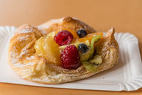 Fruit served on a pastry on a paper plate