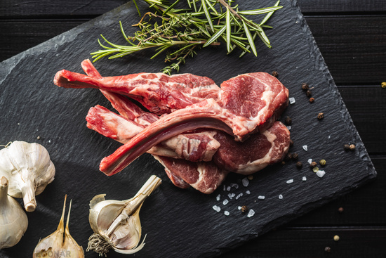 Slices raw lamb chops on black table.