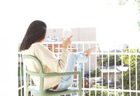 Woman with glass of wine chilling on balcony