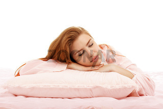 Young beautiful girl sleeps in the bed hugging a pillow on his stomach. Healthy sleep.