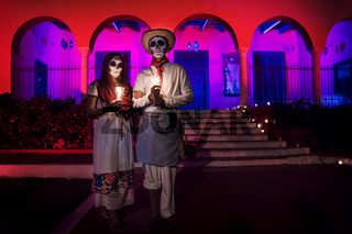 Customed man and woman with with mexican traditional white clothes and scarves and skull make-up in front of red pink lightened building with arches at the event for dias de los muertos at the Festival Des Las Animas at the Cementerio General, Merida, Mex
