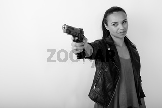 Studio shot of young Asian woman aiming handgun at distance ready to shoot against white background
