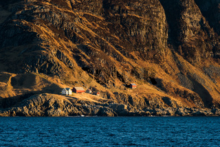 Steep cliff on the coast with small houses in stinted landscape in Norway on bright sunny day seen from boat