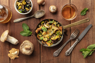 An overhead photo of a rustic mushrooms and olives saute with mint, with white wine