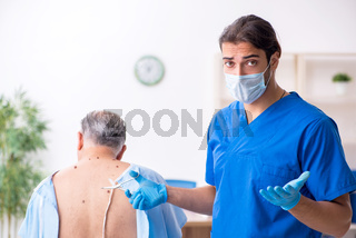 Old man visiting young male doctor dermatologist