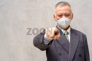 Stressed mature Japanese businessman with mask pointing at camera outdoors
