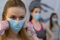 Putting on medical face protective mask athletic girls in sports out fits standing in yoga class, standing one after another in selective focus. Group of young sporty people practicing yoga lesson