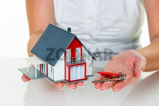 Immobilienmaklerin mit Haus und Schlüßel