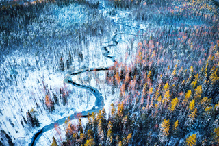 River in winter forest at sunset time
