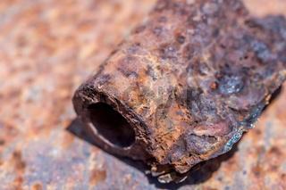 Teil einer verrosteten Türangel auf alten Rostblech