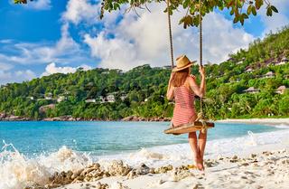 Woman swinging at tropical beach, Seychelles.