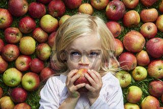 little girl lying on the grass with apples
