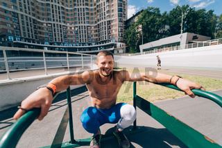 Strong man doing exercises on uneven bars in outdoor street gym.