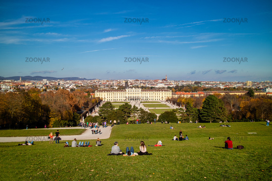 Sitting people on a grass before Schonbrunn Palace in Vienna, Austria.