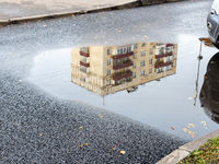 puddle with reflection of municipal urban house