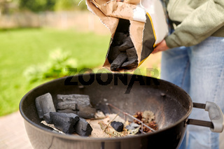 close up of man pouring charcoal to brazier