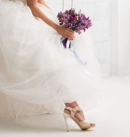 Beautiful bride with bouquet on a swing in studio