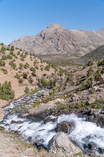 The beautiful mountain trekking road with clear blue sky and rocky hills and fresh mountain stream in Fann mountains in Tajikistan