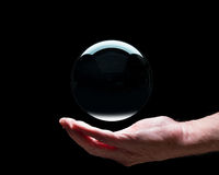 Hand holding a crystal glass forecasting ball with black center to allow easy composites