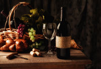 Wine still life on a rustic wood table with warm afternoon window light. An old fashioned cork screw