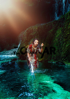 Woman with sword in lake near waterfall.