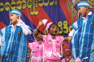 Boys and girls in traditional burmese dresses dancing on stage at a new year celebration at Bilu Kyun, Ogre Island, Mon State, Myanmar