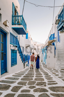 Mykonos Greece, couple man and woman on vacation at the Greek Island Mykonos, girl in dress at the white streets of little venice Mykonos