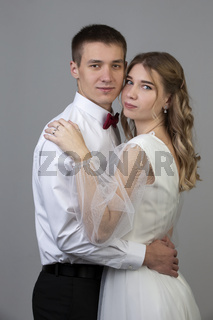 Classic vertical portrait of the bride and groom on a gray background.