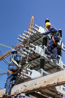 Electricians working on high voltage power lines