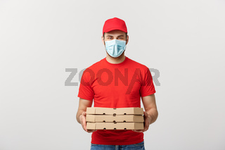 Online delivery and Coronavirus Concept. Cheerful young deliveryman in face mask holding pizza boxes while isolated on white studio background
