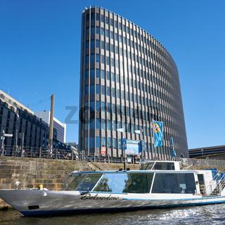 Ausflugsboot auf der Spree in Berlin und modernes Bürohaus