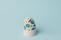 Painted chicken egg in floral pattern. DIY craft for easter holidays with kids. Botanical decoration. Minimal easter egg on blue background. Craft for spring holidays