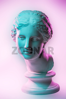 Statue of Venus de Milo. Creative concept colorful neon image with ancient greek sculpture Venus or Aphrodite head. Webpunk, vaporwave and surreal art style. Pink and green duotone effects.
