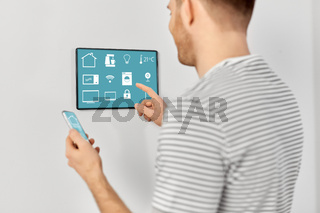 man with smartphone and tablet pc at smart home