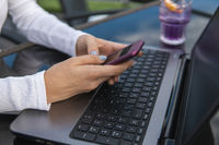 Modern business woman is reading incoming sms message on smartphone or watching broadcasting online on modern mobile phone while sitting in caffe with a laptop. Female student sitting in coffee.