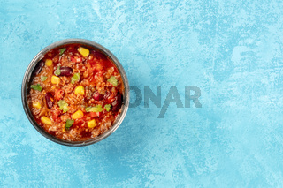 Chili con carne, a Mexican stew with beans, minced meat, corn, and chilli peppers, overhead shot on a vibrant blue background with a place for text