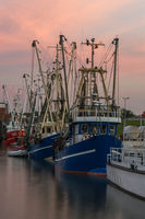 Fishing boats in the harbor of Dornumersiel at dusk, East Frisia, Lower Saxony, Germany