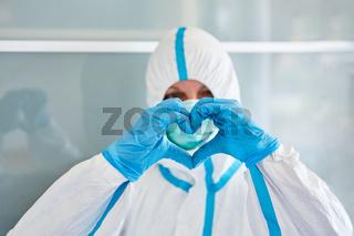Klinikpersonal formt Herz mit Händen vor Gesicht als Coronavirus Unterstützung